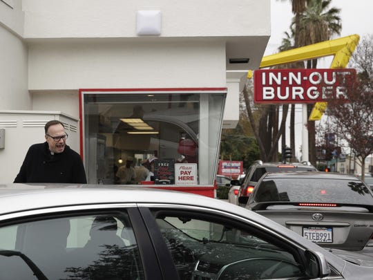 Father Jim Sichko pays for the meals of drive-thru customers Dec. 5 in Los Angeles. Sichko has a 50-state congregation and a simple mandate from the pope: Go forth and do good deeds.