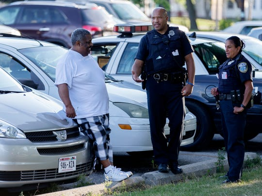 Police share a laugh with a man during a game at Meaux Park in Milwaukee.