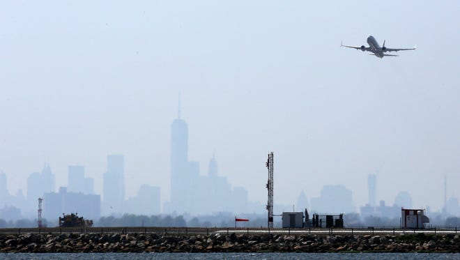 An aircraft takes off from New York's John F. Kennedy Airport against a hazy backdrop of the city skyline, May 25, 2015.
