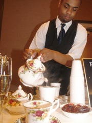 Vinnie Howard, son of Convent Station's Cosy Cupboard owner James Howard, pours a precisely prepared cup of tea.