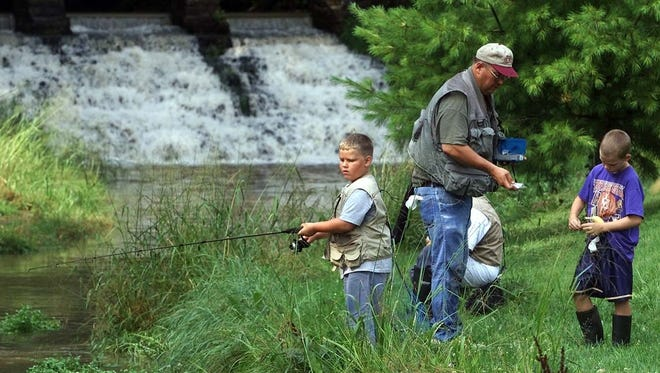 A family fishes on the stream next to the Decorah Fish Hatchery in 2002.