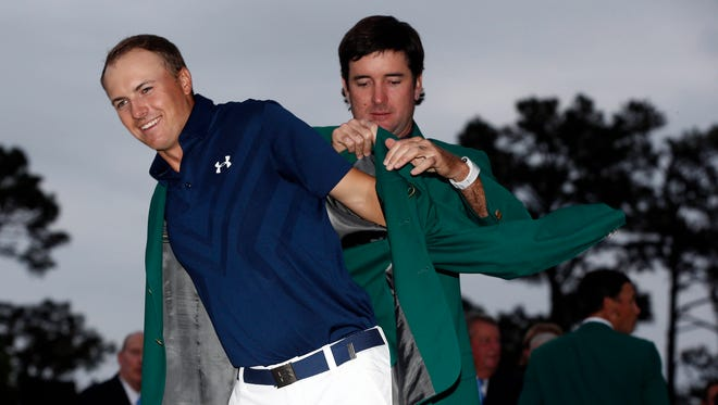 2014 champion Bubba Watson (right) helps 2015 champion Jordan Spieth into a green jacket after Spieth won The Masters golf tournament at Augusta National Golf Club.