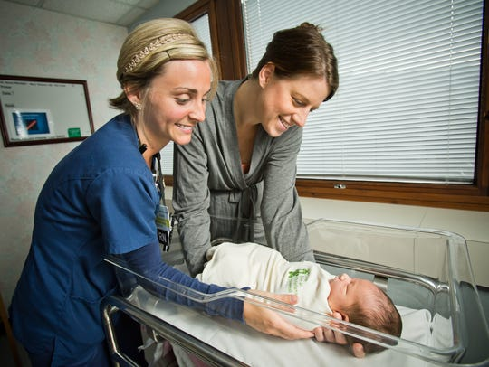 Dawn M. Jennings, RN, shows new mom Stephanie Forester