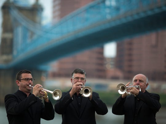 Cincinnati Symphony Orchestra trumpeters (from left:) Christopher Kiradjieff, Acting Associate Principal, Douglas Stephen Lindsay, Acting Principal Jackie & Roy Sweeney Family Chair, and Steven Pride playing the introduction of Aaron Copland's Fanfare for the Common Man in front of the John A. Roebling Suspension Bridge.