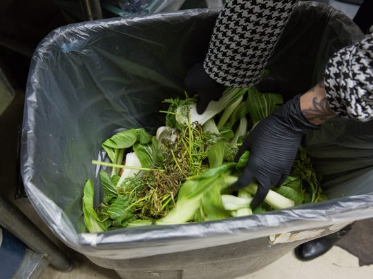 Corinne Holvick, the marketing manager at Mountain View Market Co-op, pulls clippings and other plant material in a compost can, explaining where the materials come from in the store and where the compost goes after this container, Tuesday January 10, 2017.