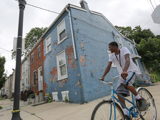 A cyclist rides past an abandoned row home on the corner of Lamotte and E. 22nd St.