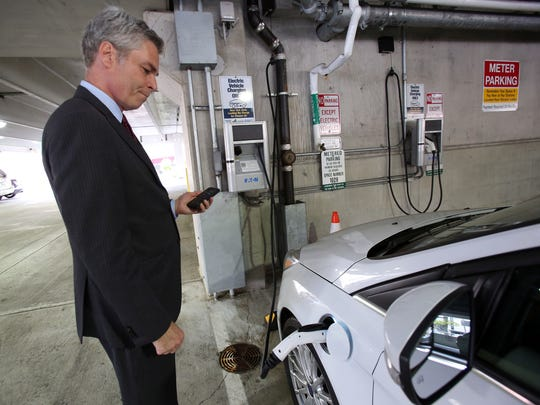 Mayor Tom Roach demonstrates how to use an electric car charger at the Lyon Place municipal garage in White Plains.
