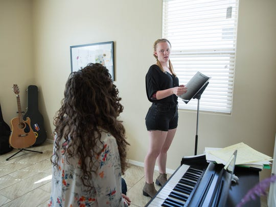 Torrie Hughes, a student in the Theater department at New Mexico State University, talks with Annie Pennies during her vocal lesson at Pennies' home studio.