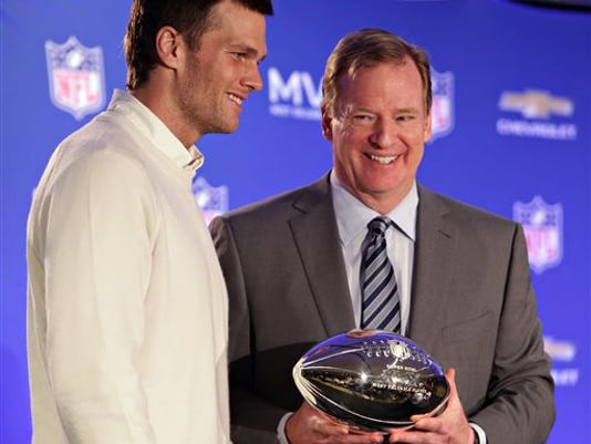 In this Feb. 2, 2015, file photo, New England Patriots quarterback Tom Brady, left, poses with NFL Commissioner Rodger Goodell during a news conference where Brady was presented the Super Bowl MVP in Phoenix, Arizona. Brady's four-game suspension for his role in using underinflated footballs during the AFC championship game last season was reversed by a federal judge Thursday.