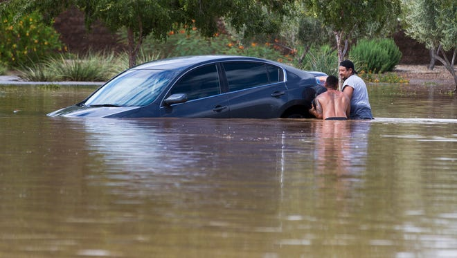 Joseph Meza Jr. (left) and Ramon Fores help rescue a woman trapped in flood waters on 103 Ave and Lower Buckeye Rd. in Tolleson September 8, 2014. They floated her car to higher ground where she was able to walk out.