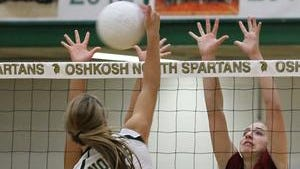 Oshkosh North's Cassie Buerger tips the ball over the net against a fond du Lac attempted block Thursday.