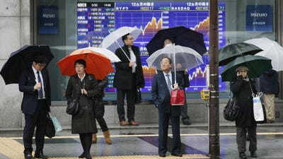 People stand in front of an electronic stock board of a securities firm in Tokyo. Asian stock markets were boosted Monday by expectations of economic stimulus in China after manufacturing continued to weaken in March. European shares fell after a eurozone manufacturing survey reinforced expectations of a slow recovery.