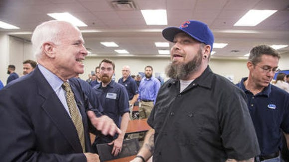 Sen. John McCain jokes with Randall Cook after an event in Mesa. Cook's cap prompted McCain, R-Ariz., to quip that anyone who shows up in Chicago Cubs hat again will be ejected. But years ago, McCain considered the Cubs his favorite team.