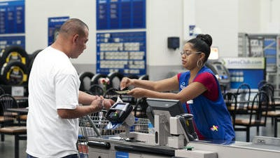 In this June 5, 2014 photo, Conquisia Tyler, right, gives change to a customer at Sam's Club in Bentonville, Ark. U.S. consumers stepped up their spending slightly in May, boosted by a jump in auto sales and higher income.