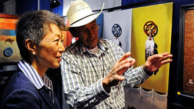 Jane Chu, chairwoman for the National Endowment for the Arts, speaks with Richard Red Owl about his acrylic paintings during the Northern Plains Indian Art Market on Sunday, Sept. 21, 2014, at the Best Western Plus Ramkota Hotel Exhibit Hall in Sioux Falls, S.D.