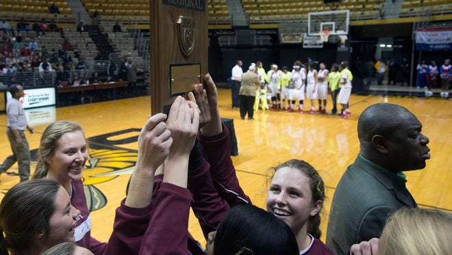 Montgomery Academy celebrates as they receive the region trophy after Montgomery Academy defeated Midfield 60-35 in the AHSAA Class 3A Central Regional Championship on Thursday, Feb. 19, 2015, at the Dunn-Oliver Acadome in Montgomery, Ala.