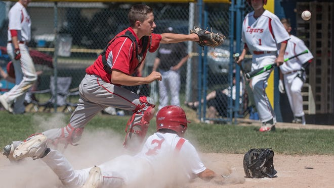 St. Philips's Ryan Reincke dives into home plate for a score against Tekonsha in district baseball at Climax-Scotts on Friday.