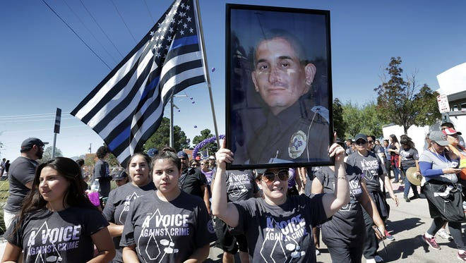 The family of Officer David Ortiz carriez his portrait on the Help, Hope, Healing 10-mile walk ending at the Crime Victims' Memorial at Yucca Park Sunday. More than 300 walkers showed their support to end crime in El Paso.