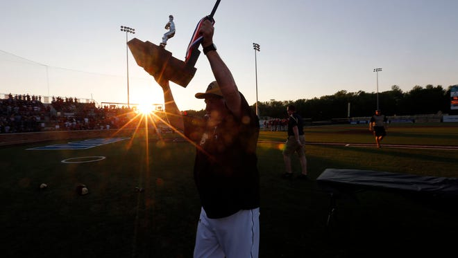 Franklin High School baseball coach Jim Hughes raises the second place trophy following the 2015 state championship game. Hughes now has 900 career victories.
