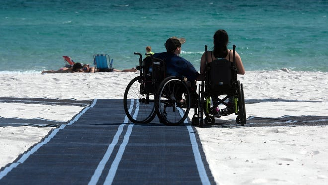 John Wood and Brianna Tran enjoy Navarre Beach unaided and closer to the shoreline than ever before Friday, March 23, 2018. Alexander and others like him can now use the new Mobi-Mat installed at the Santa Rosa County Beach to access the shore.
