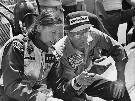 Janet Guthrie with car owner Rolla Vollstedt sitting on pit wall in 1976.