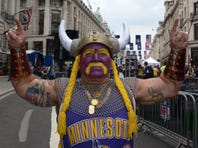 """Michael Hopson is dressed as """"Super Fan"""" as he walks in Super Bowl Village, Friday, Feb. 3, 2012, in Indianapolis, Ind."""