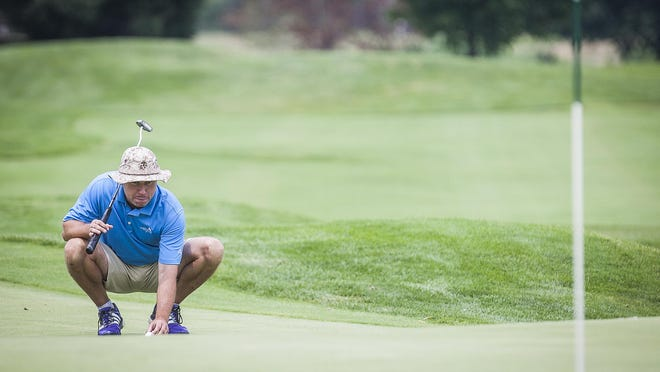 Chadwick Long sizes up a putt in the Muncie District Golf Association championship Saturday.