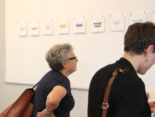 A gallery visitor views work by former GCAE artist-in-residence