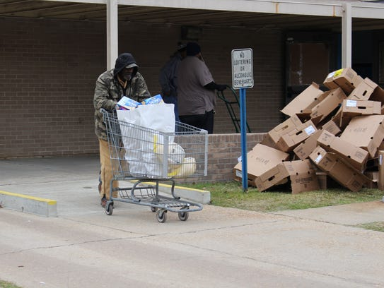 A volunteer pushes sacks of food through the parking