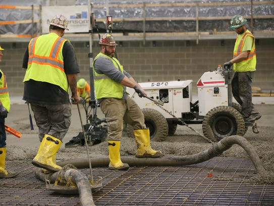 Workers at the new Milwaukee Bucks arena pour the concrete