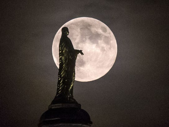 The full moon silhouettes the statue of the Virgin