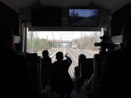 (left to right) Northjersey.com's Paul Berger looks out onto the railroad tracks from the last car of an Amtrak train with Amtrak Executive Vice President Stephen Gardner and CEO Charles Moorman during a Northeast Corridor train ride from Trenton to New York City on Wednesday, April 19, 2017.