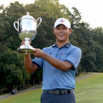 Si Woo Kim poses with the Sam Snead trophy after winning