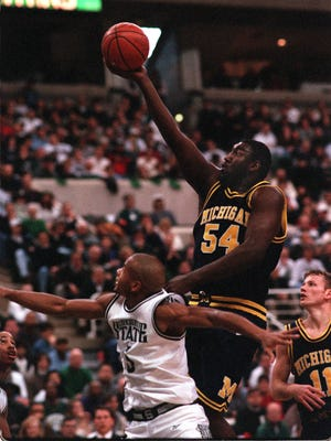 Michigan's Robert Traylor barrels over MSU defender Ray Weathers during Tom Izzo's first game as head coach against Michigan on Jan. 13, 1996.