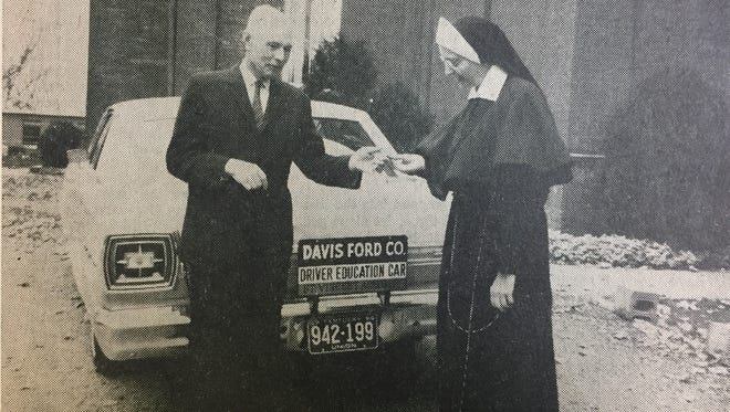 A. B. Davis, of Davis Ford Company, presents the keys to a 1966 Ford Galaxy to Sister Raymunds, principal at St. Vincent Academy. The car was presented to the Academy for use in the school's driver training program in November of 1965.