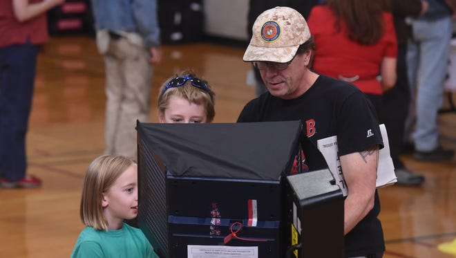 James Mack's children Charlotte, 9, left, and Clark, 12, watch as he votes in at Reno High School on Nov. 8, 2016.