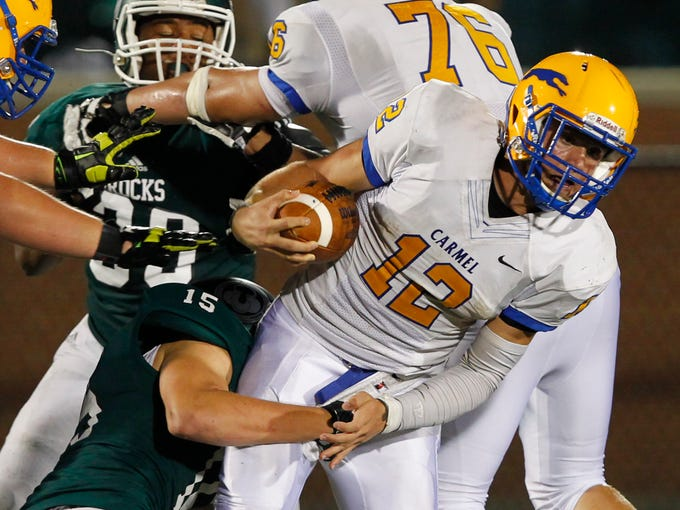 Carmel High School's Michael Viktrup (12) is tackled by Trinity High School's Alex Reisert (15) during the second half of play at Trinity High School in Louisville, Kentucky.       August 29, 2014