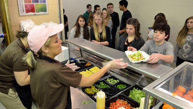 Students line up to get a Subway-style sandwich Tuesday at Port Huron Northern High School. Port Huron Area School District serves free lunch and breakfast to its students through a grant funded program.