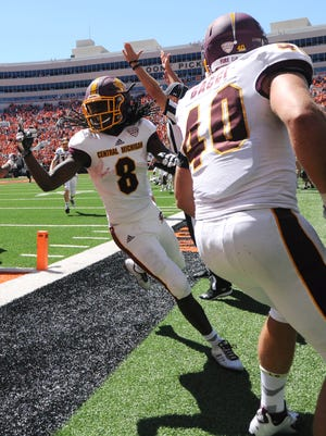 A referee signals a touchdown as Central Michigan wide receiver Corey Willis (8) celebrates with his teammate running back Joe Bacci (40) after scoring the winning touchdown.