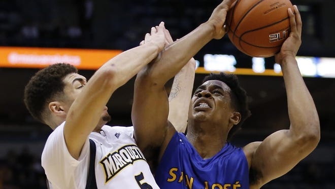 San Jose State's Princeton Onwas is fouled as he drives against Marquette's Sandy Cohen III (left) during the second half Tuesday in Milwaukee.