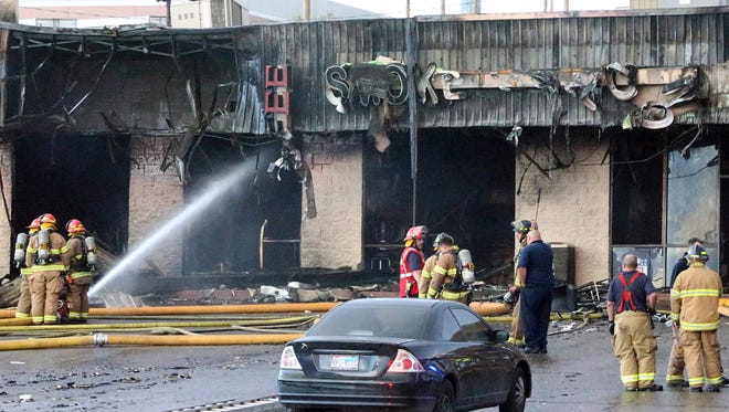 Firefighters extinguish smoldering areas of a business shopping strip along the 1300 block of N. Lee Treviño Monday evening.