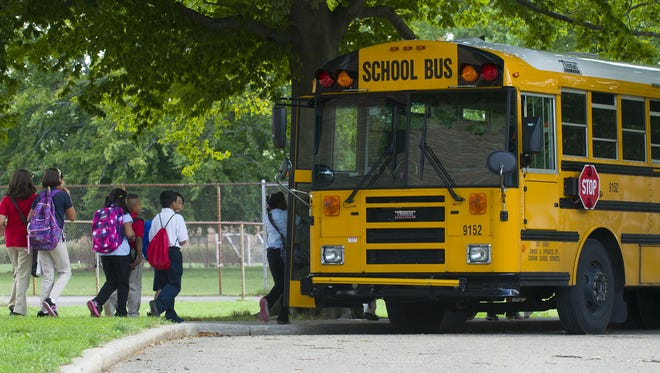 Students walk to waiting school buses.