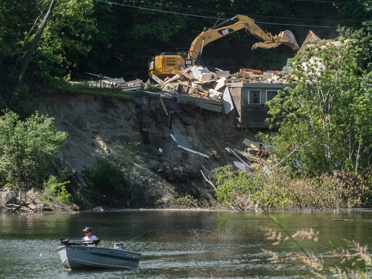 A demolition crew on Monday, June 20, 2016, began taking down a home on Plattsburg Avenue in Burlington that had been in danger of falling into the Winooski River since May 24 after the embankment the home's foundation was washed away under.