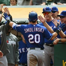 OAKLAND, CA - SEPTEMBER 18:  Jake Smolinski #20 of the Texas Rangers is congratulated by teammates after he scored against the Oakland Athletics in the top of the first inning at O.co Coliseum on September 18, 2014 in Oakland, California.  (Photo by Thearon W. Henderson/Getty Images)