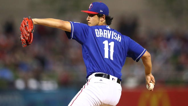 Texas Rangers pitcher Yu Darvish throws against the San Francisco Giants during a Cactus League spring training game at Surprise Stadium.