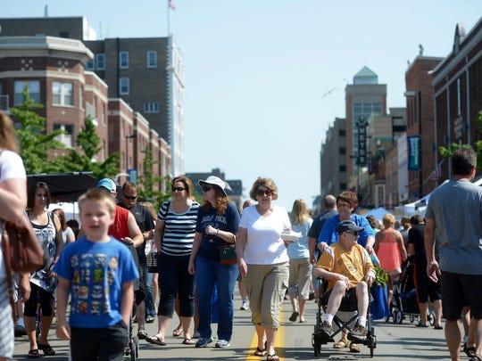 People walk around the Saturday Farmers Market on Washington Street in downtown Green Bay.