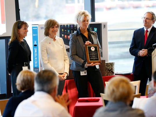 Corning Inc.'s Kathy Eisele, who helps organize blood drives for the company, accepts a plaque on behalf of the diesel division for donating the most blood in 2016.