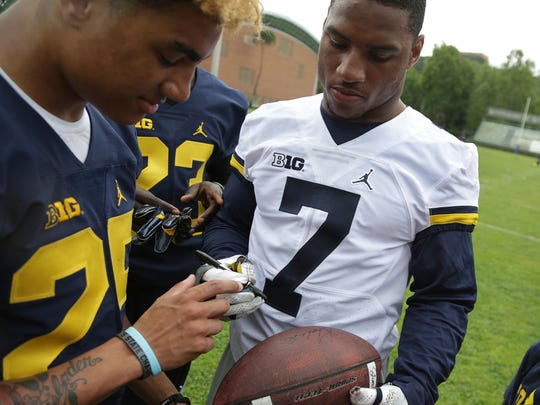 Michigan wide receiver Nate Johnson, left, and safety Khaleke Hudson sign footballs for fans after their first day of practice in Rome at Giulio Onesti Training Center on April 27, 2017.