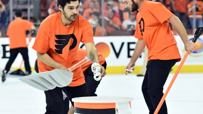 Members of the Flyers' ice crew pick up wristbands that were thrown onto the ice during the third period against the Washington Capitals Monday.
