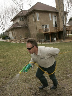 TruGreen ChemLawn employee Steven Schmidt applies fertilizer at a residence. Wisconsin residents can add their name to a registry that would require professional lawncare companies to notify them when spraying pesticides.